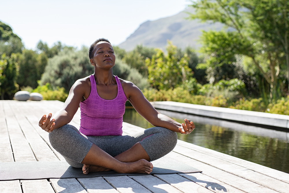 Black women with purple athletic tank top and grey pants siting cross-legged on a yoga mat with eyes close. Image to illustrate playful psychology