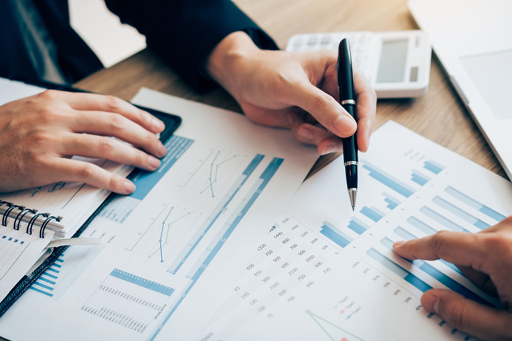 A stock image a close of people writing and observing a variety of graphs.