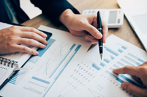 photo of two people looking at charts