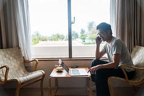 窓のそばで仕事する男性
