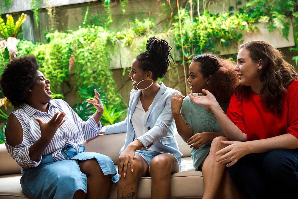 Four women chatting and laughing together.