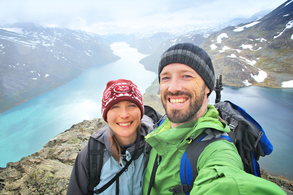 smiling couple on a mountain peak