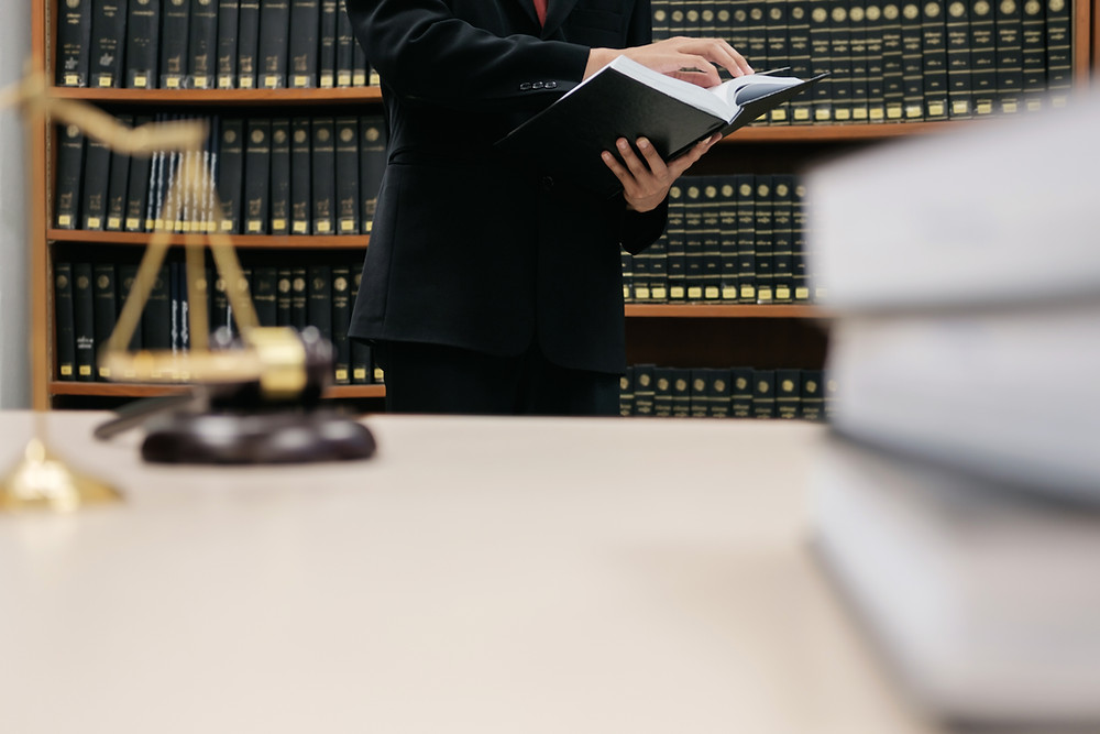law library with criminal defense attorney and law books