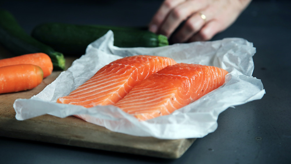 raw salmon fillets on a wooden chopping board