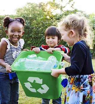 Niñas cargando una papelera de reciclaje