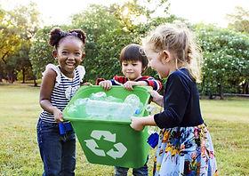 Filles portant un bac de recyclage