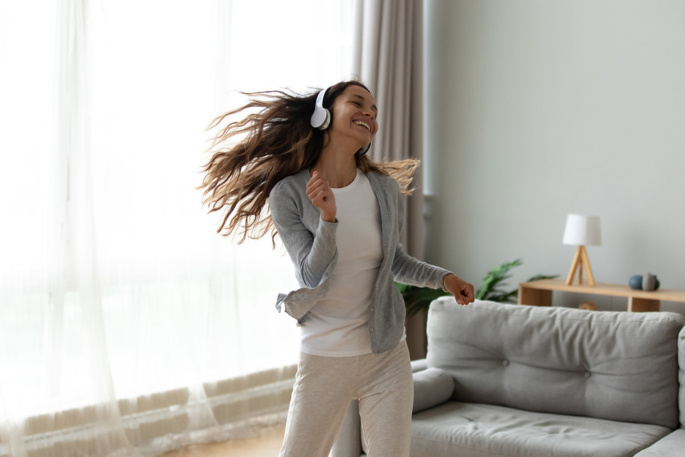A girl dances to music in the living room with headphones on.
