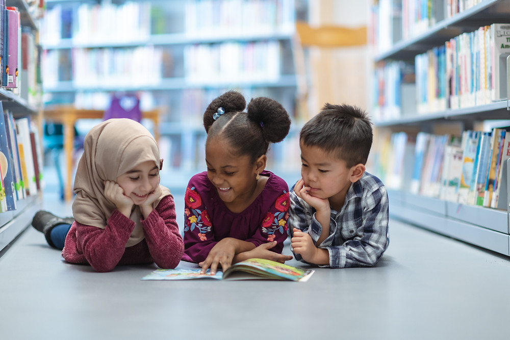 Child wearing a hijab, Black girl with two afro puffs, and Aisan boy all lying on thier stomachs sharing a book together