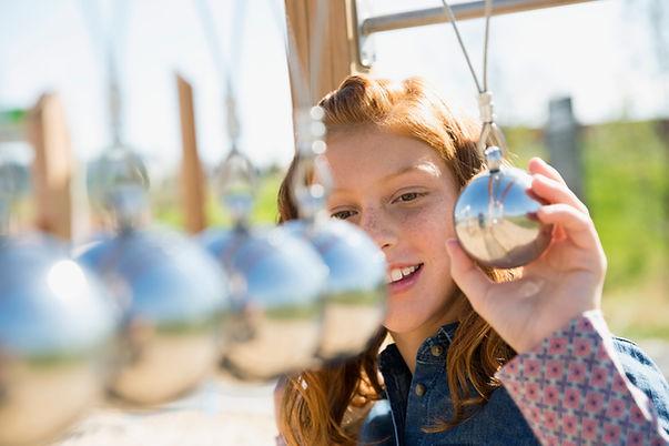 Uma menina olhando para um modelo de pêndulo