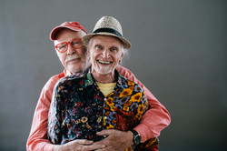 Gay older adult couple embracing and wearing hats and flowery shirts