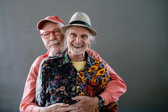 zwei ältere Männer lächeln in die Kamera, sie tragen buntes Gewand