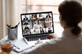 Uma mulher de costas trabalha em um notebook. Na tela, aparecem várias pessoas. Ela está em uma reunião de trabalho.