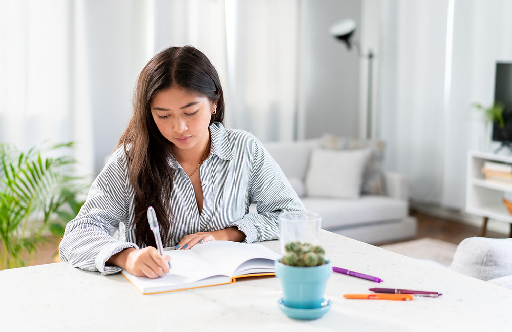 Confident woman writing out her fitness plan to meet her goals