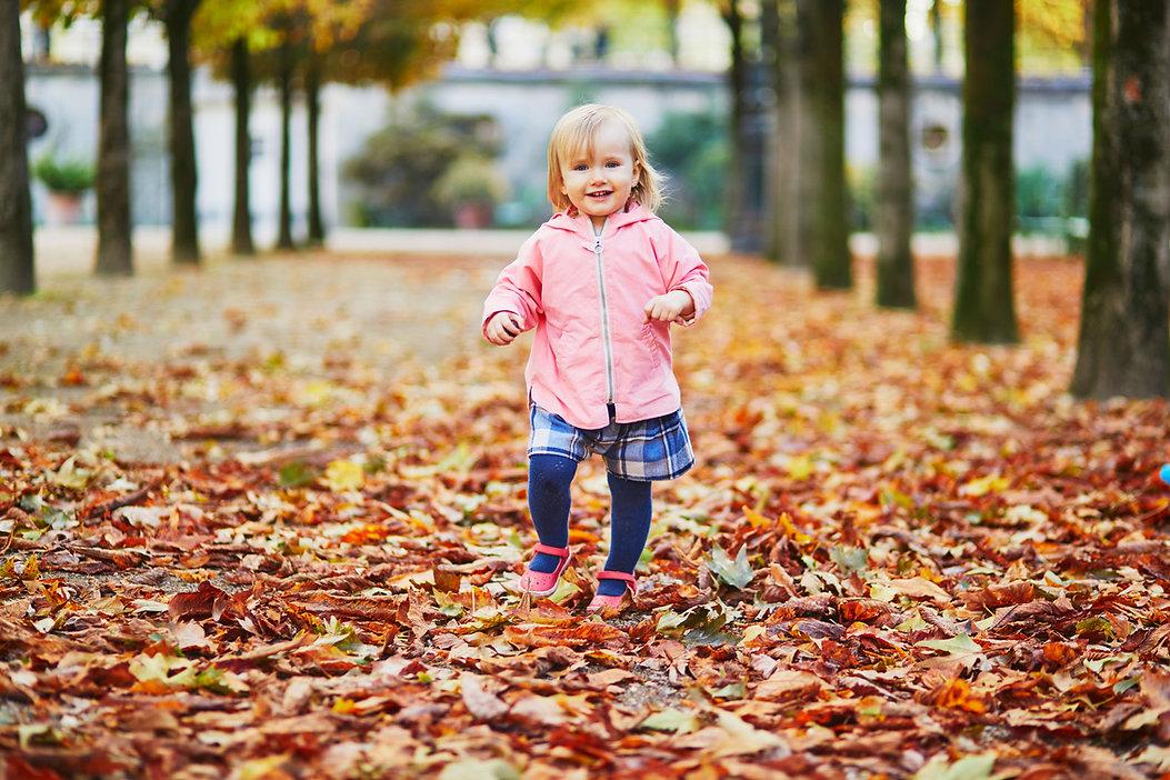 Petite fille marchant sur les feuilles d