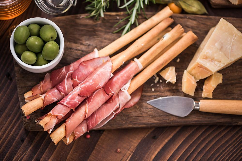 Tabua com queijo, azeitonas e grissinis com presunto