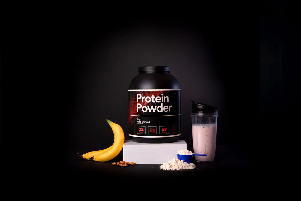 Protein Powder Container with banana, almonds and blended pink shake drink