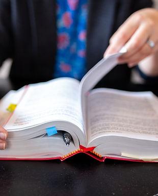 Femme consultant un livre juridique