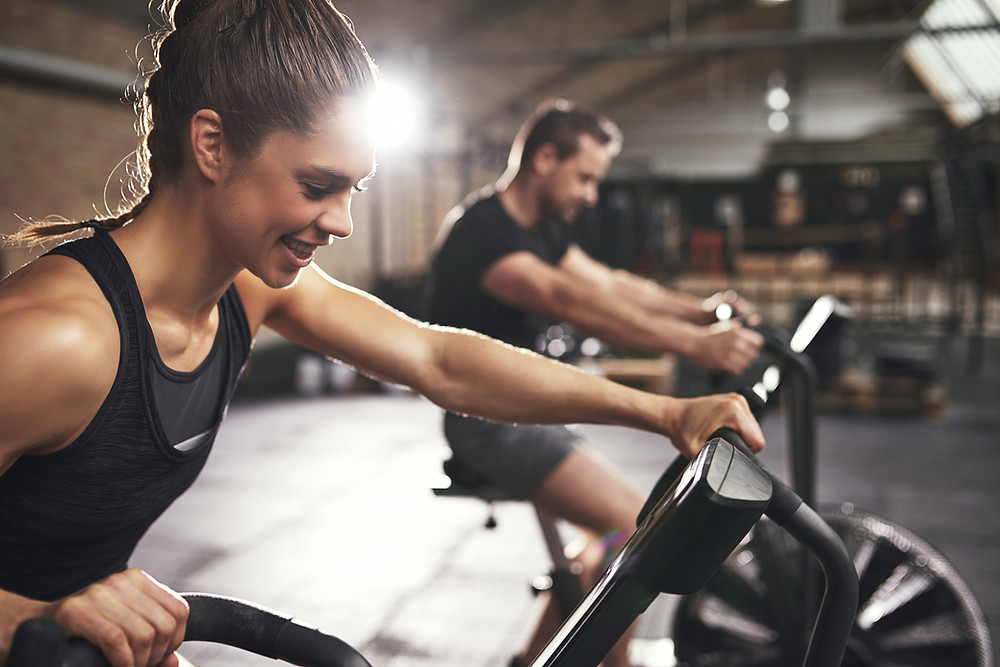 a faster way to fat loss. And image of two exercisers working out on airdyne bikes. As part of a fat loss workout they are completing a series of fat-loss exercises.