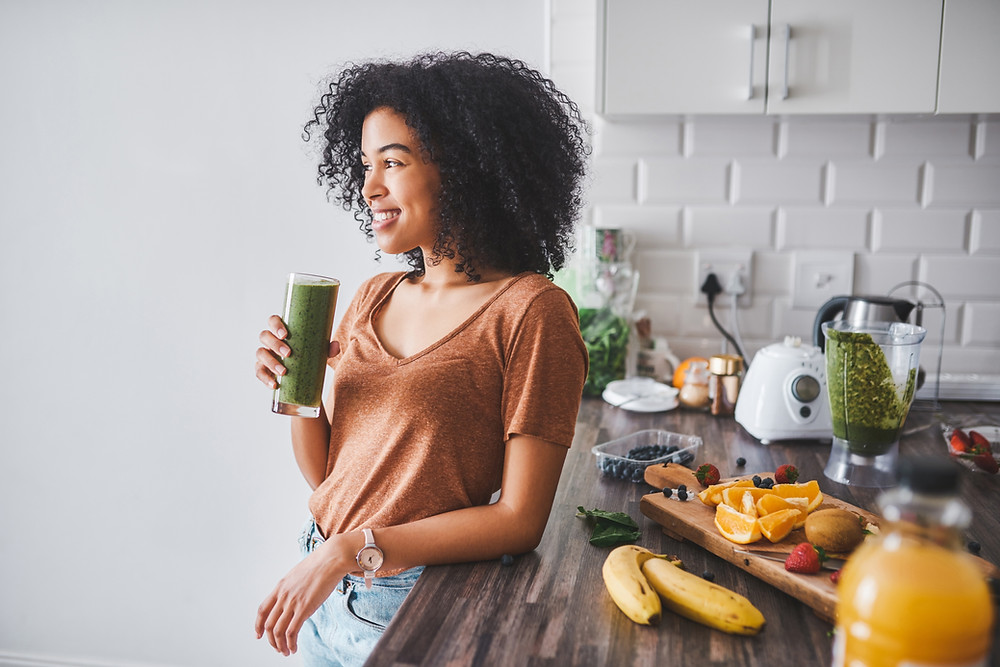 a woman about to drink a health vegetable and fruit smoothie.