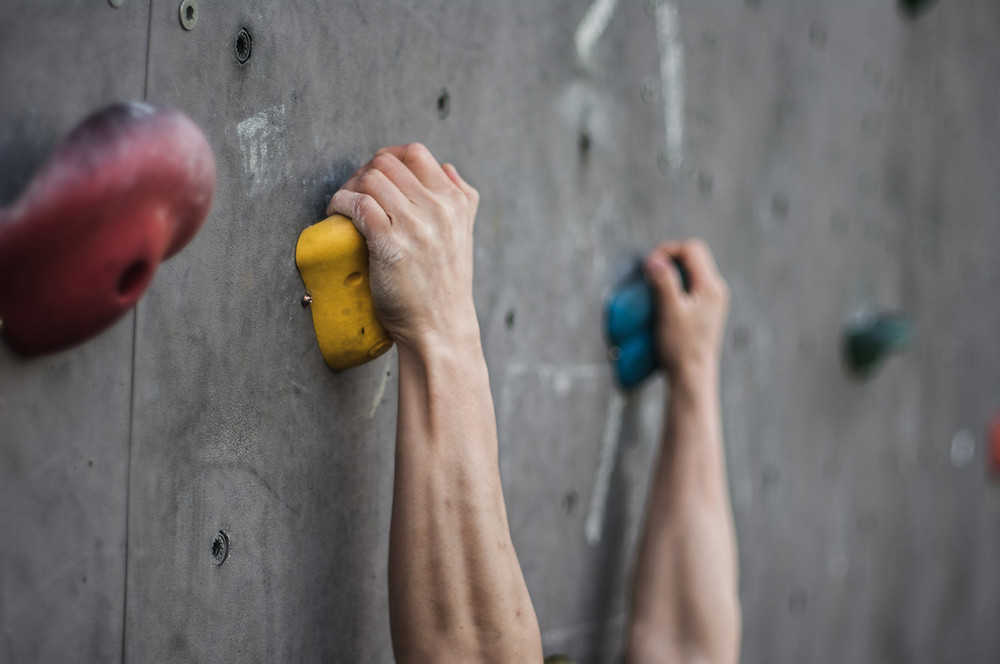 climbing gripping on to holds at a climbing wall