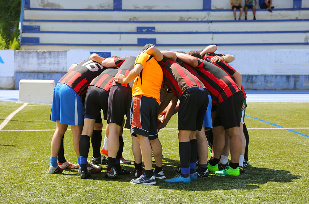 A group of people in sports jerseys and athletic wear huddling.