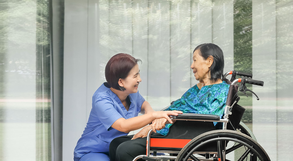 Nurse talking to patient in wheelchair