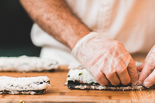 A personal chef is rolling sushi for a dinner party