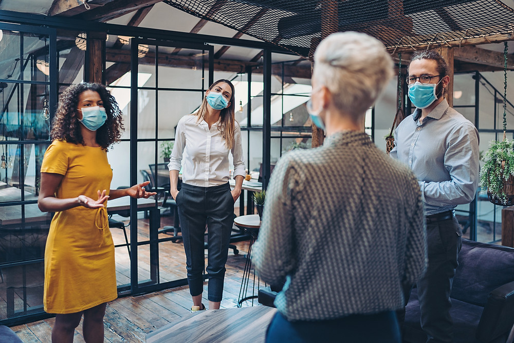 Four people in a general workspace all wear masks and stand at a safe distance apart from each other to keep each other safe from COVID
