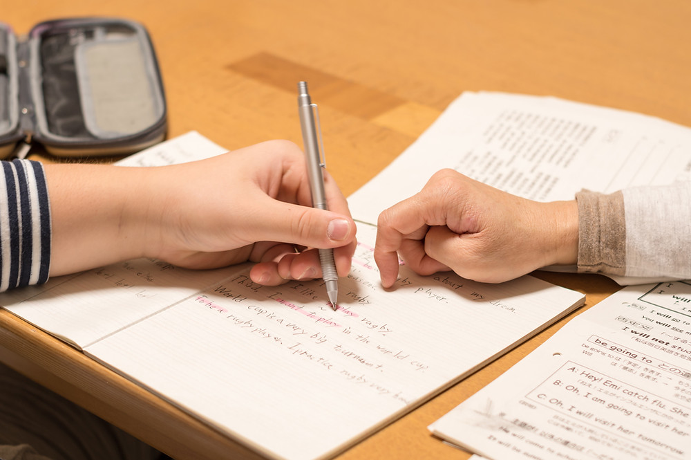two hands signing paperwork