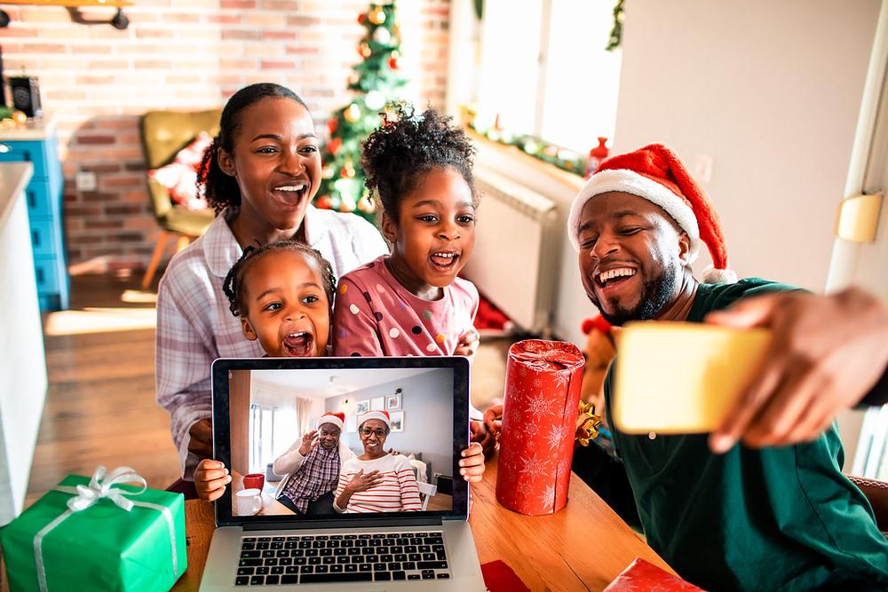 Famille célébrant Noël à distance des grands-parents connectés.