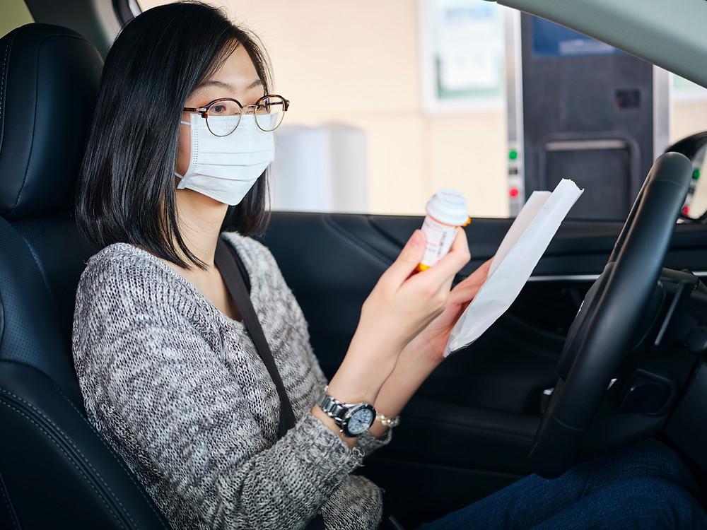 Mujer oriental en coche con mascarilla leyendo prospecto medicinal