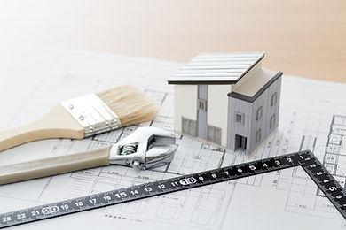 建物の模型と設計図と塗装用ブラシ