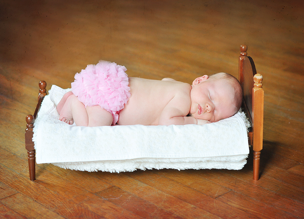 Newborn baby girl on baby bed