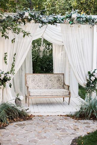Podium mit weißen Vorhängen und einer doppelsitzbank. Dahinter ein Traubogen
