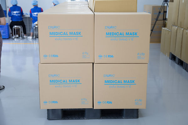 """Cartons of medical masks with people facing away in the background wearing vests with the brand name """"Protec"""""""
