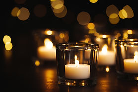 Burning candle on table against blurred background. Funeral symbol.jpg