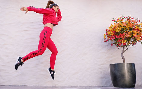 woman-in-red-tracksuit-jumping-near-wall