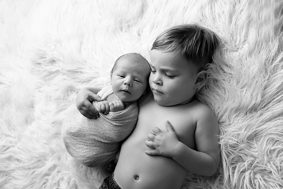 baby snuggles with big brother