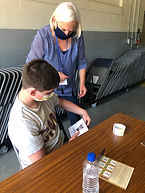 Adult volunteer helping student.