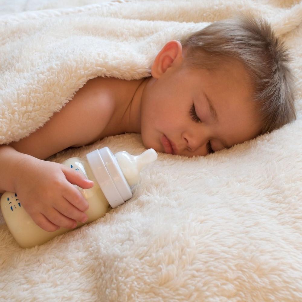 Baby sleeping with feeding bottle