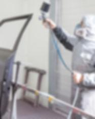 Car Body Painter Spraying Paint On Bodyw