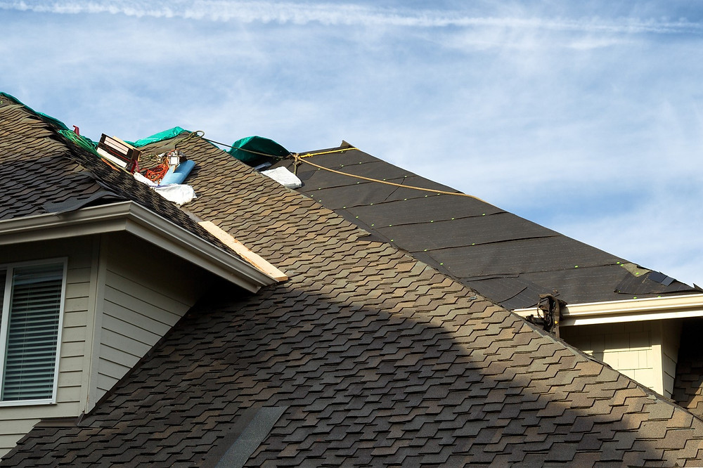 Mile High Roofing laying synthetic roof underlayment while repairing a roof.
