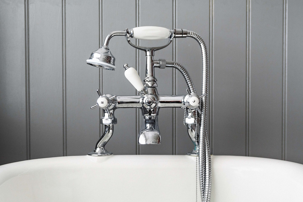 A white and silver showerhead in front of a grey wall