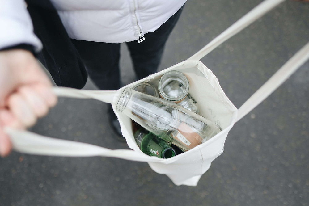 A person holding a white tote bag filled with empty bottles