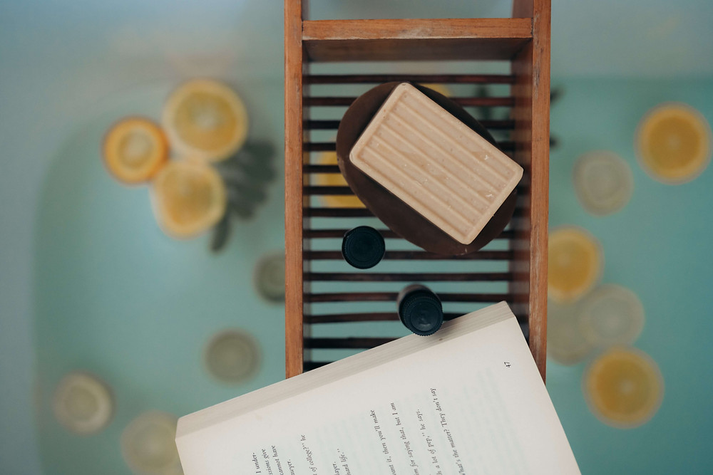 A overhead photo of a bar of soap and a book laid on a stand above a bathtub with water and orange slices