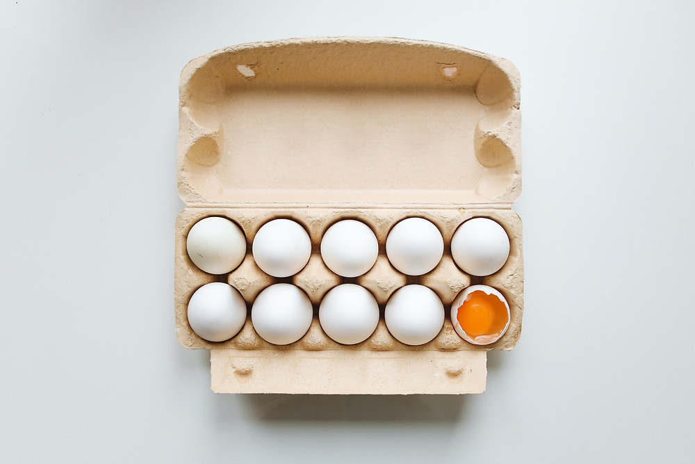 An open carton of 10 eggs in a cardboard packaging