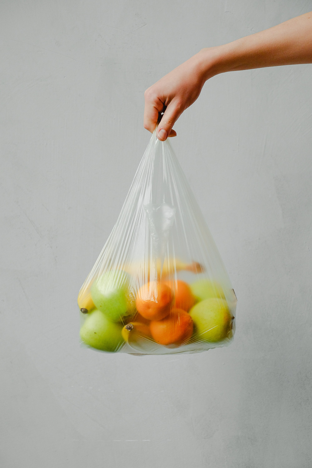 A hand holding a clear plastic bag filled with fruits (bananas, oranges and green apples)