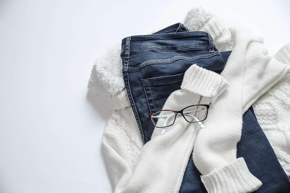 Sebuah sweter putih diletakkan dengan latar belakang putih, dilipat untuk memeluk celana jeans dan kacamata di atasnya