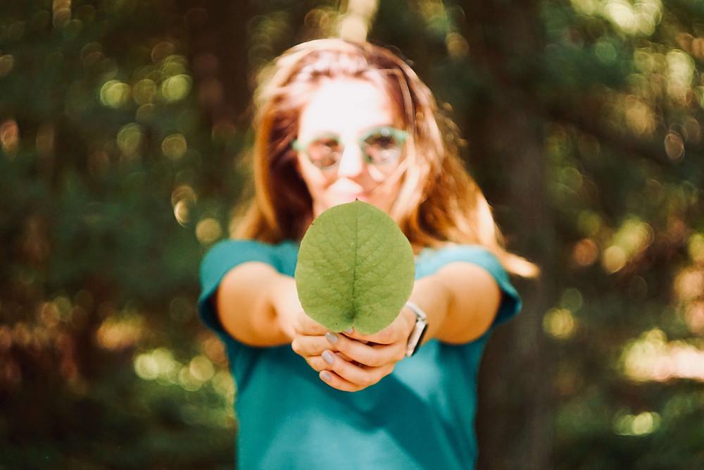 Seorang gadis menghadap kamera, mengenakan kemeja biru-hijau dan kacamata hitam memegang sehelai daun di depannya