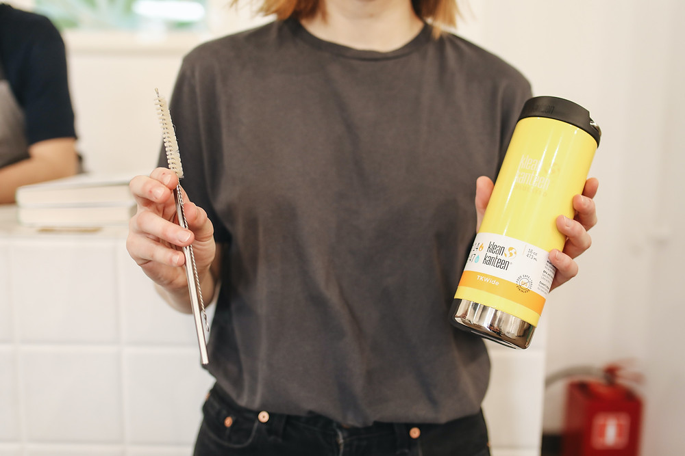 A woman holding a yellow metal thermos and a brush (made from metal) to clean metal straws